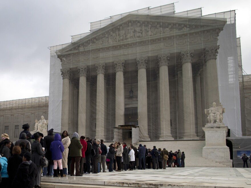 People wait in line outside the Supreme Court in February. In a landmark decision half a century ago, the justices guaranteed a lawyer for criminal defendants who are too poor to afford one.