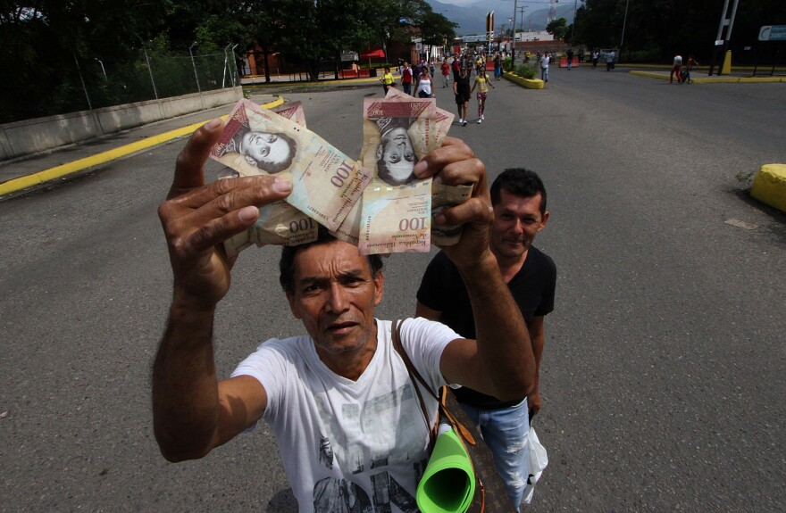 A man shows 100-Bolivar notes while crossing the Francisco de Paula Santander international bridge, linking Urena, in Venezuela and Cucuta, in Colombia Saturday, despite the border closing order issued by the Venezuelan government.