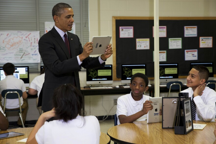 President Obama records students on a classroom iPad while visiting a seventh grade classroom before speaking about goals of connecting students to next generation broadband and wireless technology within five years on Tuesday, at Buck Lodge Middle School in Adelphi, Md.