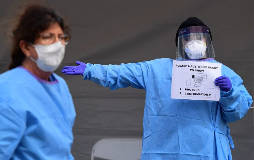 Medical personnel wear facemasks and display instructions for people arriving in their vehicles for COVID-19 testing on April 8, 2020, on the first day of testing at the Charles R. Drew University of Medicine in south Los Angeles.(FREDERIC J. BROWN/AFP via Getty Images)