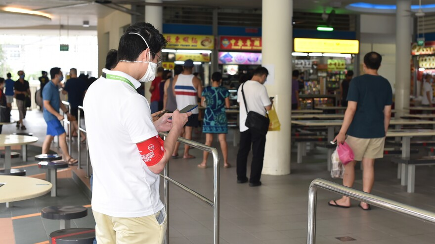 A safe-distancing enforcement officer wearing a red armband checks his phone at a food court in Singapore on Saturday. The officers have been deployed to ensure people maintain distance from one another, as Singapore grapples with a spike in coronavirus cases.