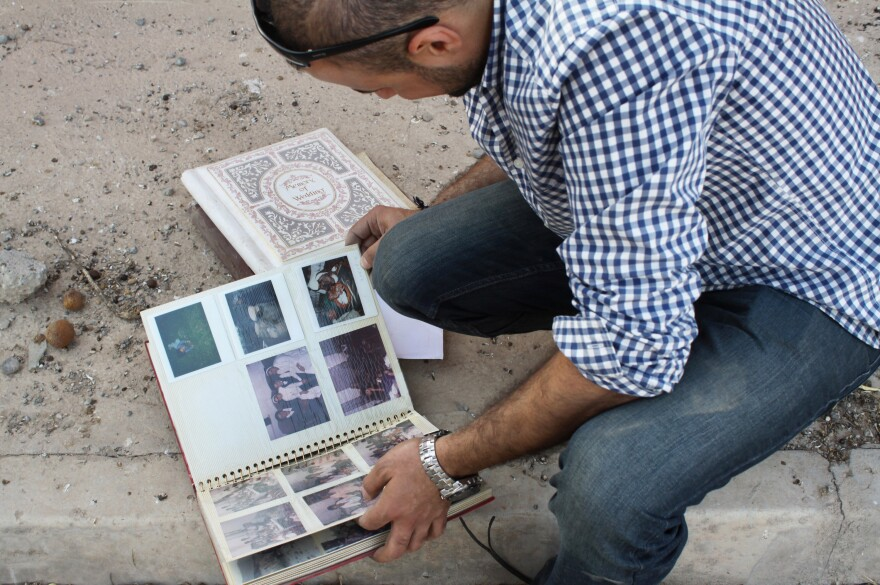Businessman Taher Bahoo lingers over family photo albums he salvaged from his home, which was ransacked by ISIS.