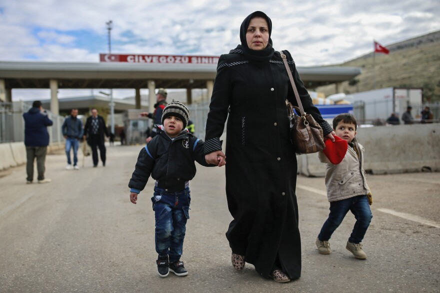 Iptisam Muhammed, 25, from Aleppo, Syria, walks with her children after crossing into Turkey at the Cilvegozu border gate on Sunday. Several people were able to cross into Turkey after they managed to leave the embattled Syrian city.
