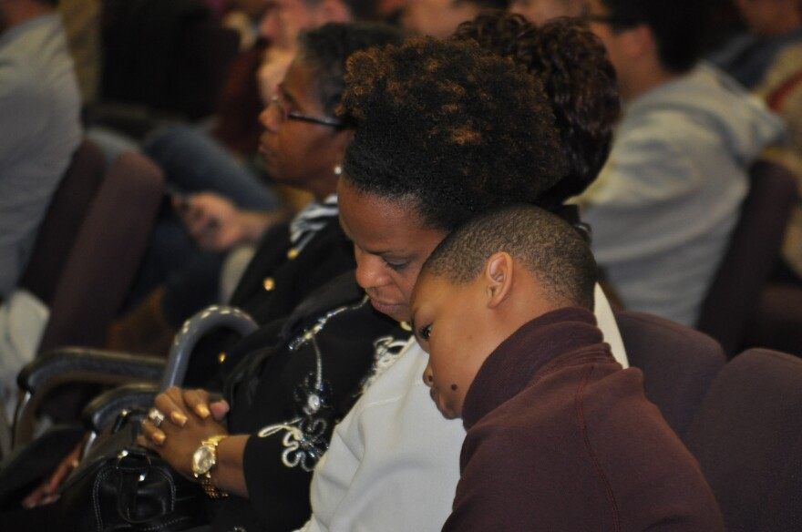 A mother and her son react to the grand jury decision, watched over livestream, at West Side Missionary Baptist Church in North St. Louis County.
