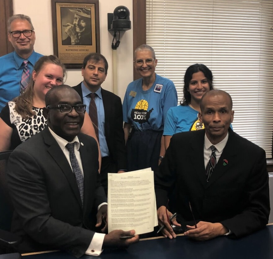 St. Louis Board of Alderman President Lewis Reed (left) poses with Ward 18 Alderman Terry Kennedy (right) and others after signing the new codes into law on July 6, 2018.