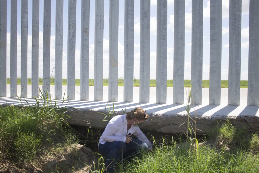 Marianna Treviño-Wright examines damage and erosion under the privately built border wall in Mission, Texas.
