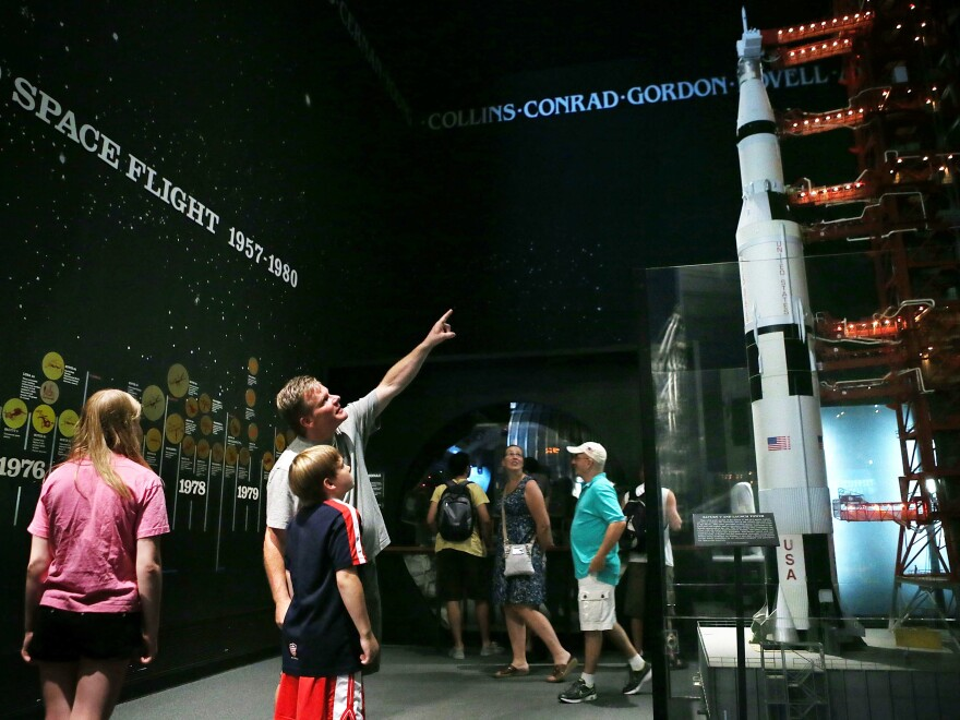 Visitors look at a model of a Saturn V rocket and its launch umbilical tower, which were used during the Apollo moon-landing program, at the Smithsonian National Air and Space Museum in Washington, D.C. Fifty years ago this July 20, Neil Armstrong and Buzz Aldrin became the first humans to walk on the moon.