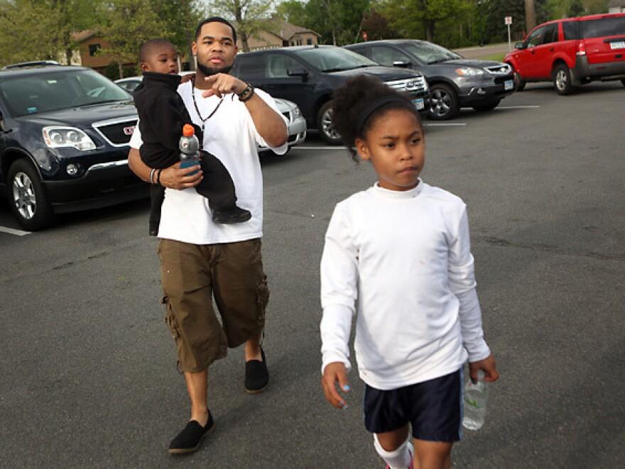 Joseph Arradondo walks with son Nasir, 2, and daughter Nevaeh, 9, before Nevaeh's soccer game.