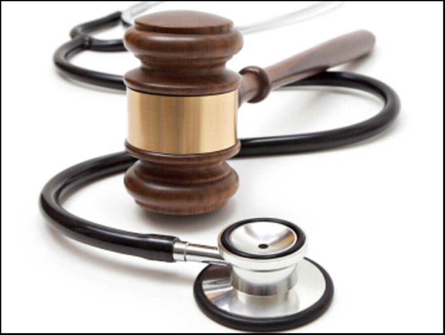 Stethoscope and gavel against a white backdrop.