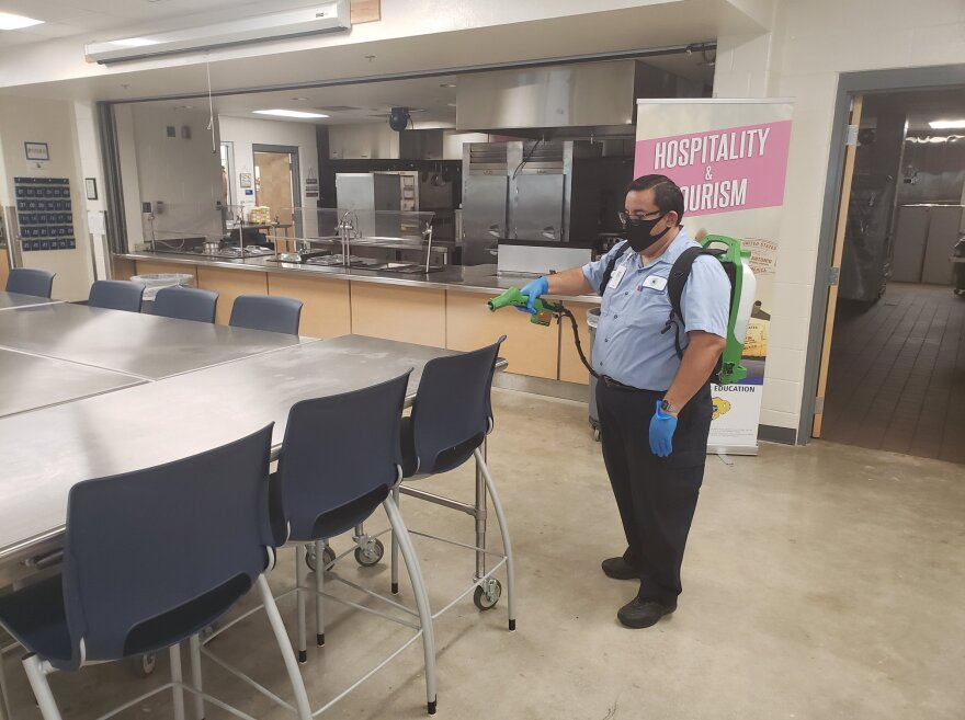 A custodian at Schertz-Cibolor-Universal City cleans a school cafeteria using a new tool purchased to enhance sanitazation during the coronavirus pandemic.