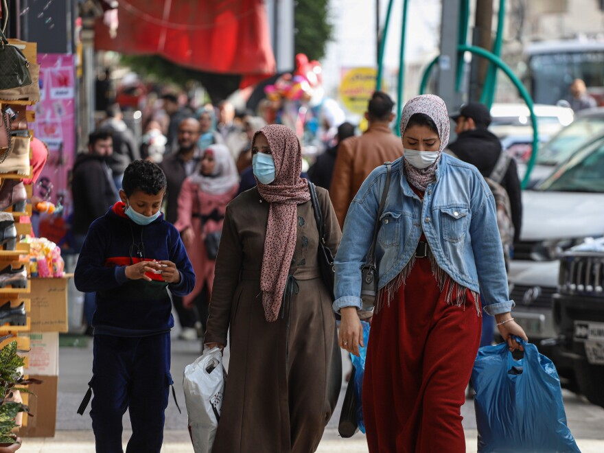 People wear face masks on a shopping street in Gaza City in January.