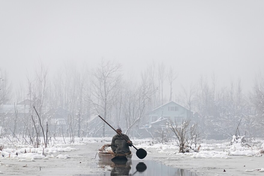 A farmer heads through the frozen waterways near the floating produce market on Dal Lake in Srinagar, the main city of India's Jammu and Kashmir state.
