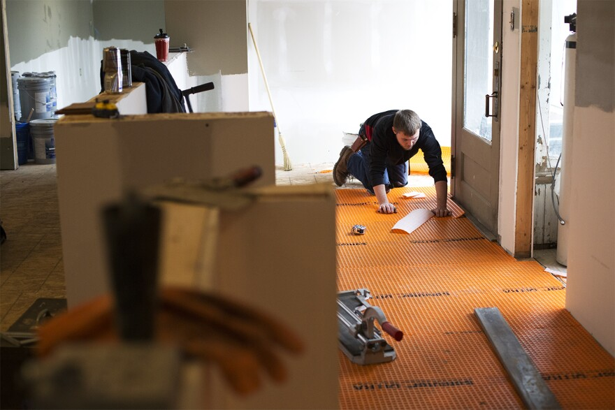 Jamen Weddle puts down new flooring on the first floor of the McHugh-Dailey building on Wednesday, Feb. 3, 2016.