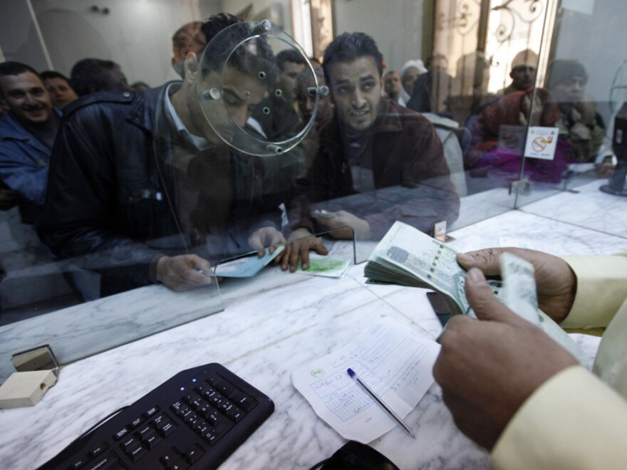 A Libyan cashier counts money as citizens queue at a bank in Benghazi on Feb. 27.
