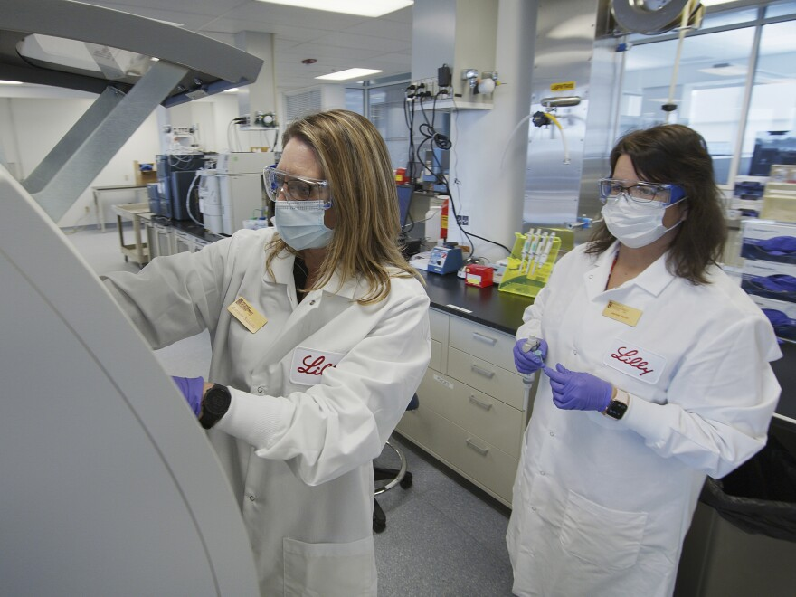 Eli Lilly researchers prepare cells to produce possible COVID-19 antibodies in a laboratory in Indianapolis. The drugmaker has asked the U.S. government to allow emergency use of its experimental antibody therapy.