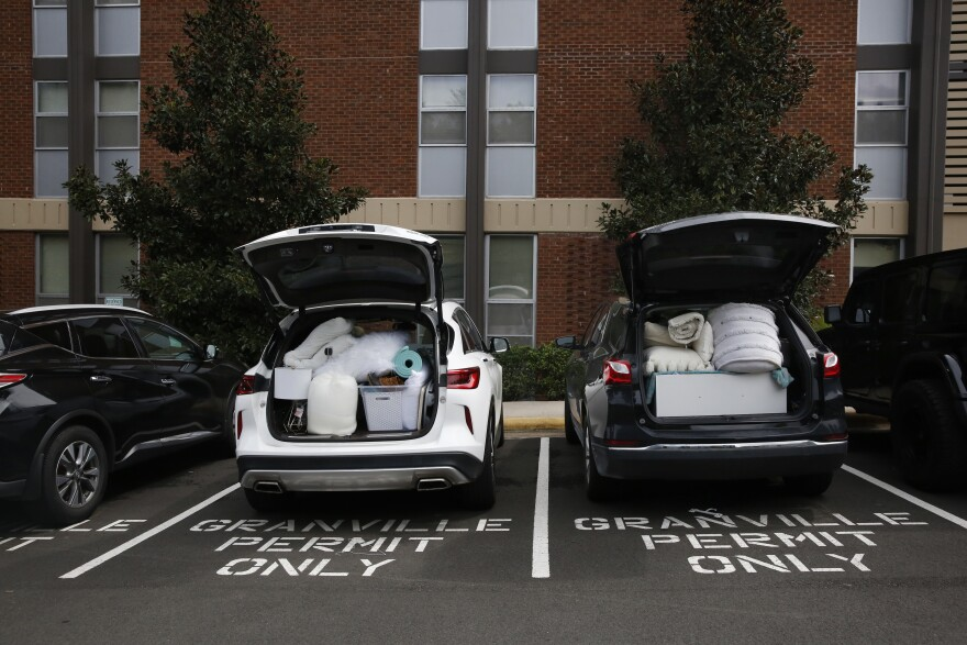 "Students pack their belongings back into cars at Granville Towers, where one of the first clusters of positive coronavirus cases was <a href=""https://alertcarolina.unc.edu/notifications/2020/08/14/cases/"">reported on Aug. 14</a>."
