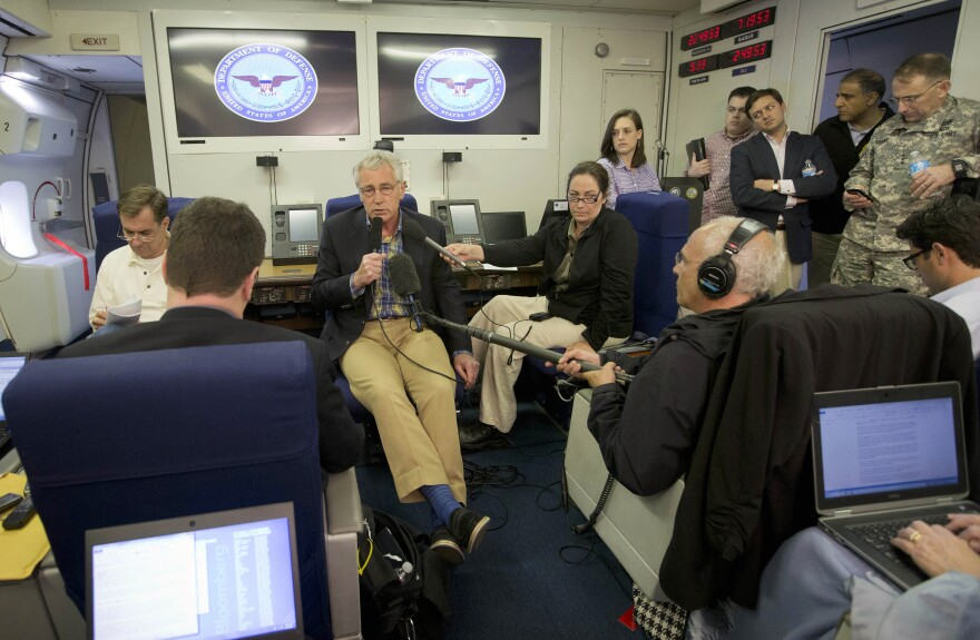 Defense Secretary Chuck Hagel, center, speaks to members of the media aboard a U.S. military aircraft on Sunday. Hagel said quick action was necessary to save Sgt. Bowe Bergdahl's life, leaving no time to disclose the administration's plans to Congress.