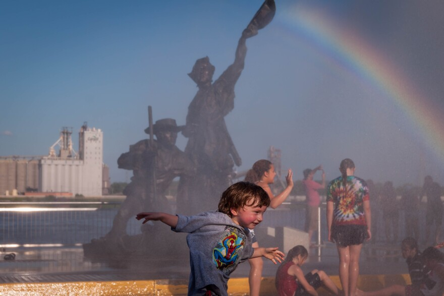 Richie Edger, 4, runs through a mister in front of the Lewis and Clark statue at Gateway Arch National Park as part of Fair St. Louis.  July 4, 2018.