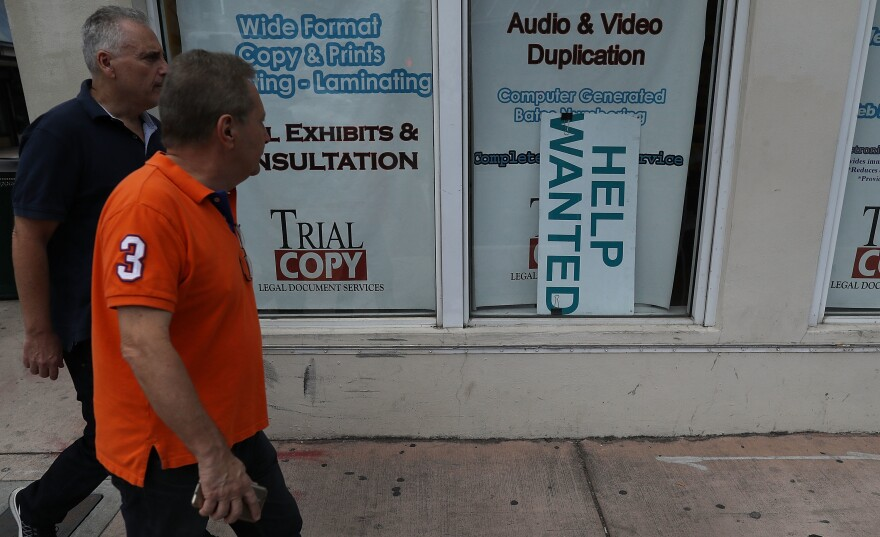 """A """"help wanted"""" sign hangs in a storefront window in Miami last month. The Bureau of Labor Statistics says nonfarm payrolls increased by 98,000 in March, far below analysts' expectations."""