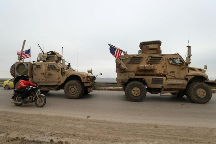 A US military convoy drives on the outskirts of the Kurdish-controlled northern Syrian city of Qamishli on February 12, 2020. (Delil Souleiman/AFP)