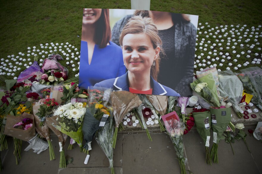 An image and floral tributes for Jo Cox, lay on Parliament Square, outside the House of Parliament in London on Friday. The 41-year-old British Member of Parliament was fatally injured in an attack on Thursday in northern England.