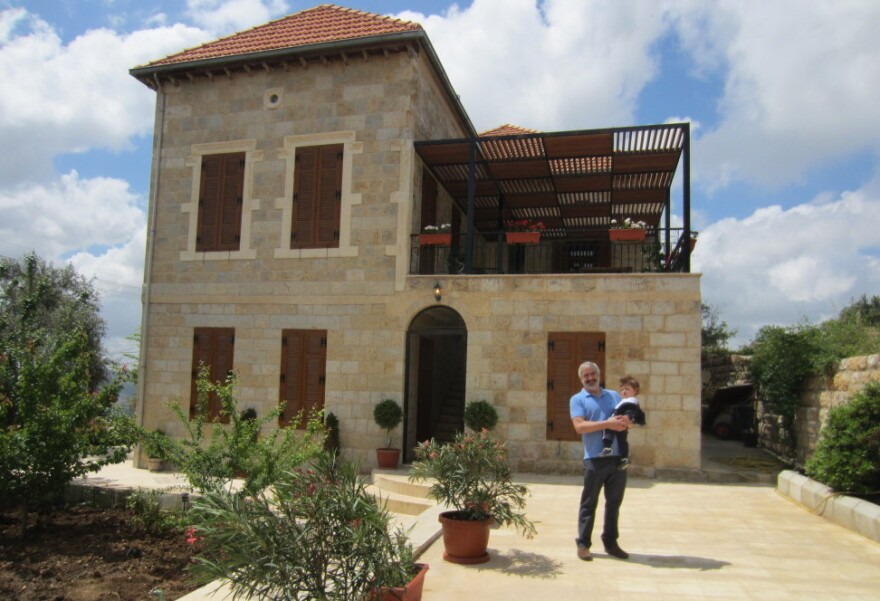Shadid holds his son in front of the family home he spent years renovating in Marjayoun, Lebanon.