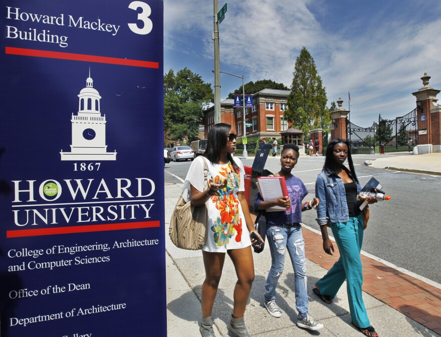 Howard University students walk near the university's main gate.