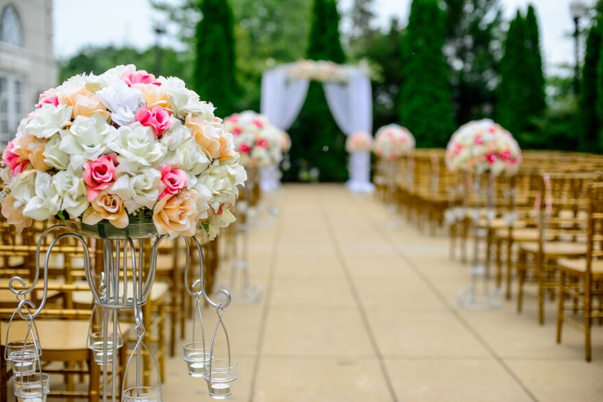 Aisles of wooden chairs and bouquets of flowers lead to an arch draped in sheer cloth. Shrubbery is in the background.