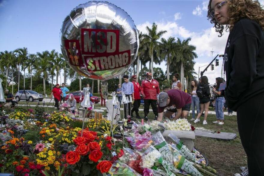 Flowers and balloons are laid at a memorial outside of Marjory Stoneman Douglas High School during the one-year anniversary of the shooting death of 17 students and faculty members at the Parkland school on Thursday, Feb. 14, 2019.
