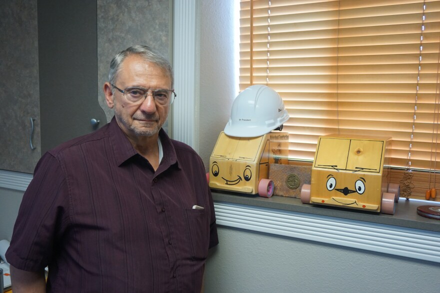 Phil Cohen with two of the toy trucks he made when he started woodworking. It was his escape from a life of drugs and crime, and now he hires people with similar backgrounds to work at his business.