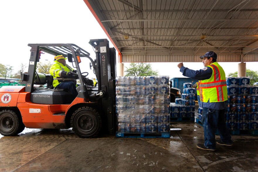 Carlos Frausto directs an incoming water shipment at the City of Austin Warehouse, one of Austin's water distribution centers, on October 24, 2018.