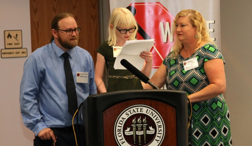 Kiersten McCans (middle) is an Honor roll elementary school student. Joined by her parents, she's speaking during last week's celebration of the 75th anniversary of the Florida Division of Blind Services and White Cane Safety Day.