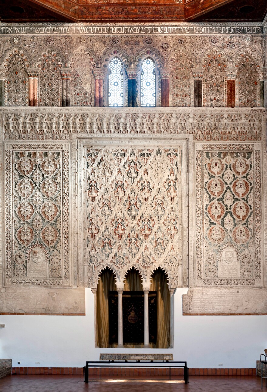 The interior of the 14th-century El Transito synagogue in Toledo, Spain. The synagogue's walls are intricately carved with Hebrew prayers, in marble and gold, and Moorish designs — representing the mix of Jewish and Arab traditions that coexisted in Spain during the Middle Ages. Here you can see the nave of the synagogue, where Torah scrolls were once kept.