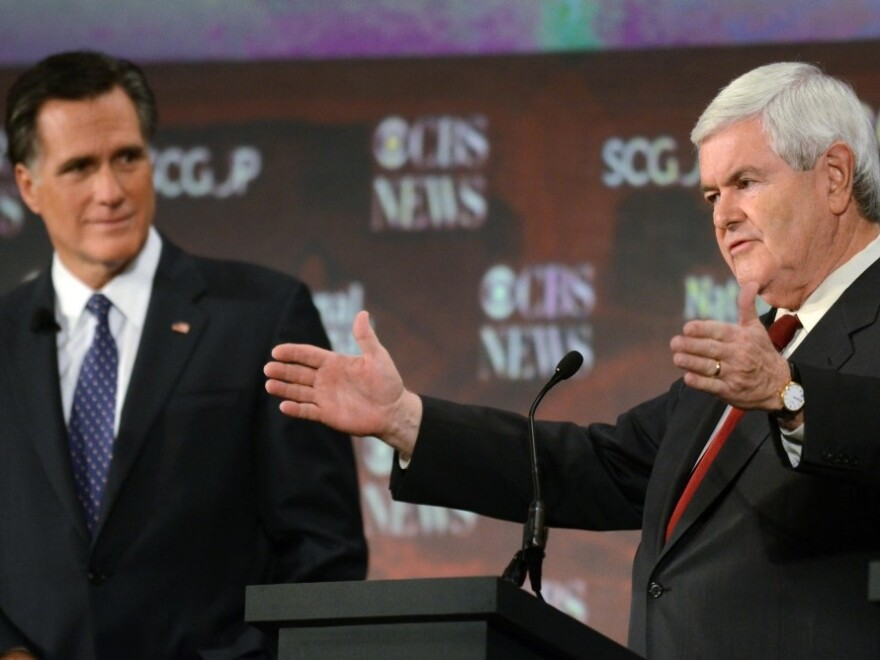 Mitt Romney watches as Newt Gingrich talks during Republican presidential debate in Spartanburg, S.C.