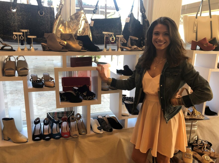 Jane Loves Shoes manager Sydney Allegri staging merchandise before re-opening.