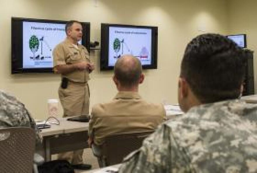 U.S. Navy Cmd. James Lawler, Naval Medical Research Bio Defense chief of clinical research, briefs a 30-person joint service medical support team in an effort to train personnel to respond quickly, effectively and safely in the event of additional Ebola cases in the United States, on San Antonio Military Medical Center, Tex., Oct. 22, 2014.