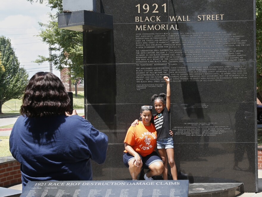 Katrina Cotton, center, of Houston poses for a photo Monday with her daughter, Kennedy Cotton, 7, at the Black Wall Street Memorial in Tulsa, Okla.