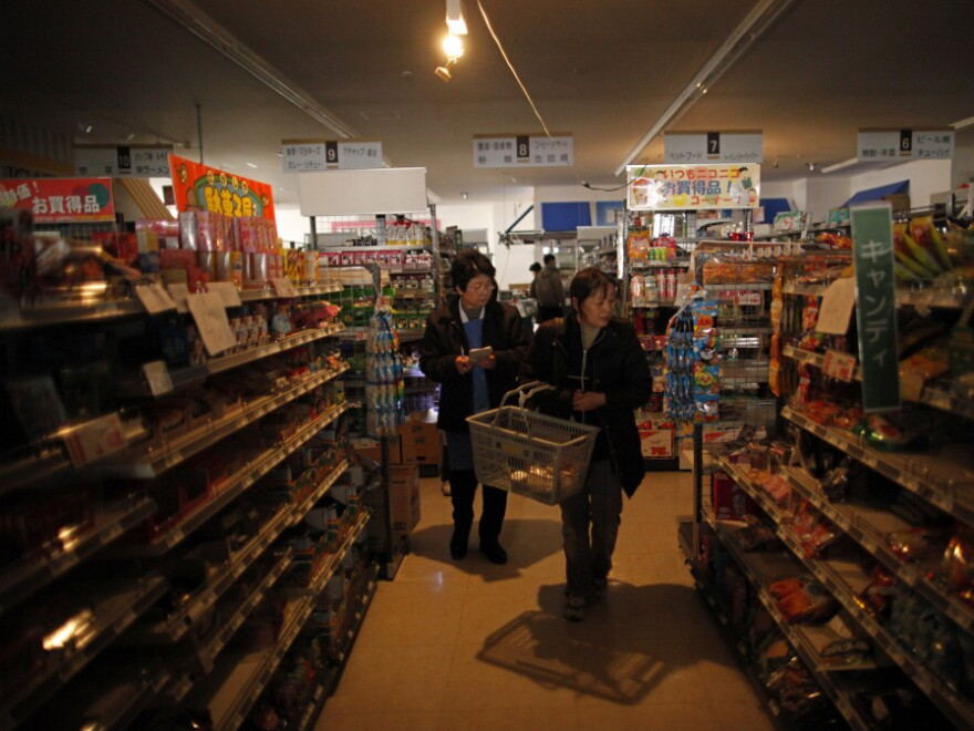 People try to browse at a supermarket with no electricity in  Ishinomaki, Miyagi prefecture, Japan. Businesses are especially worried about weathering Japan's sweltering summers without air conditioning.