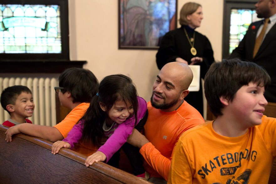 Alex Garcia jokes with his 3-year-old, AriannaLee, while sitting with his family before the start of a church service.