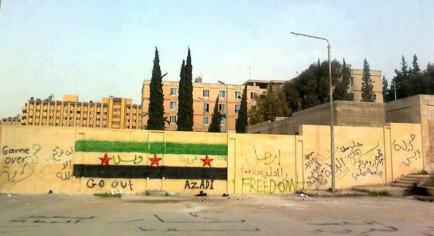 A handout picture released by the Syrian opposition's Shaam News Network shows anti-regime graffiti sprayed on the walls of Aleppo University.