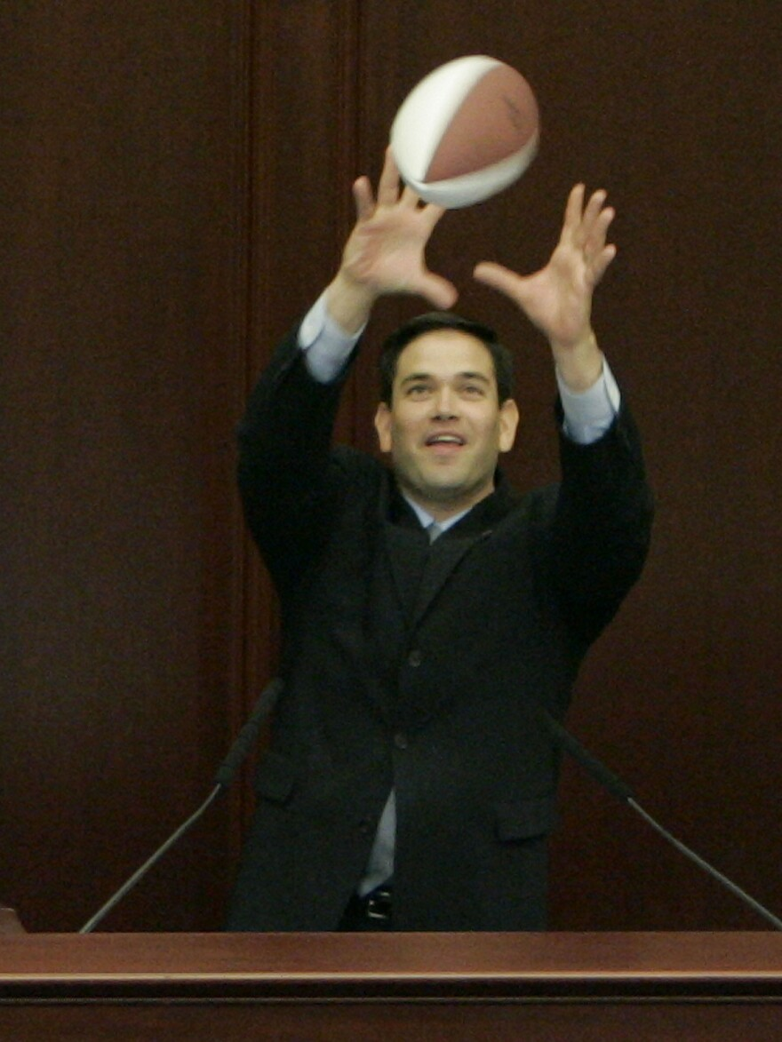 Rubio, who went to college on a football scholarship, catches a pass from University of Florida quarterback Chris Leak during Leak's visit to Florida's House of Representatives in 2007.