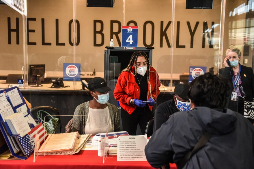 Poll workers check in a voter at the Barclays Center in New York City on Oct. 24.