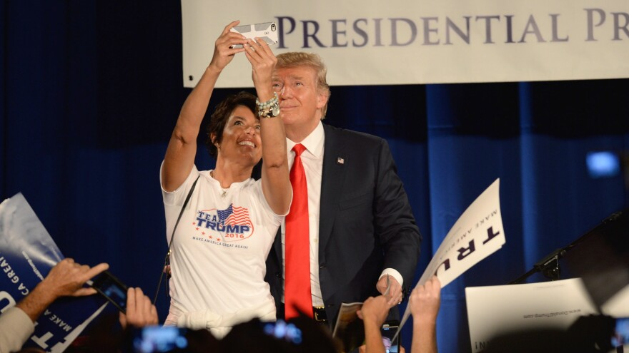 "Donald Trump poses for a selfie with a woman wearing a ""Team Trump"" T-shirt on stage at the National Federation of Republican Assemblies Presidential Preference Convention in Nashville, Tennessee."