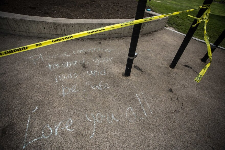 A message in chalk reminds people to wash their hands and be safe.