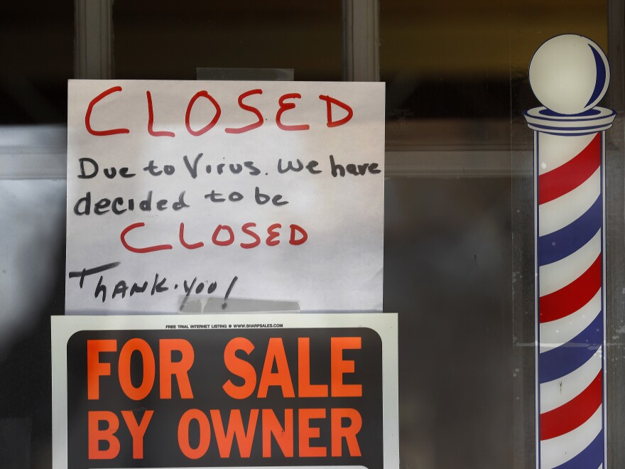 """For Sale By Owner"" and ""Closed Due to Virus"" signs are displayed in the window of Images On Mack in Grosse Pointe Woods, Mich. Congress is considering ways to help those struggling during the economic downturn and stabilize businesses hoping to reopen."