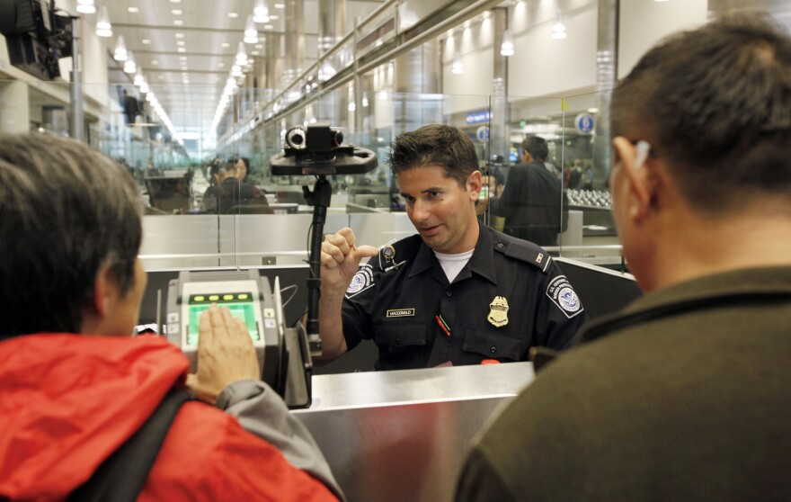A Customs and Border Protection officer explains to arriving international passengers at Los Angeles International Airport how to provide their fingerprints. While visitors are fingerprinted and photographed upon arrival in the U.S., they are currently not tracked upon departure.