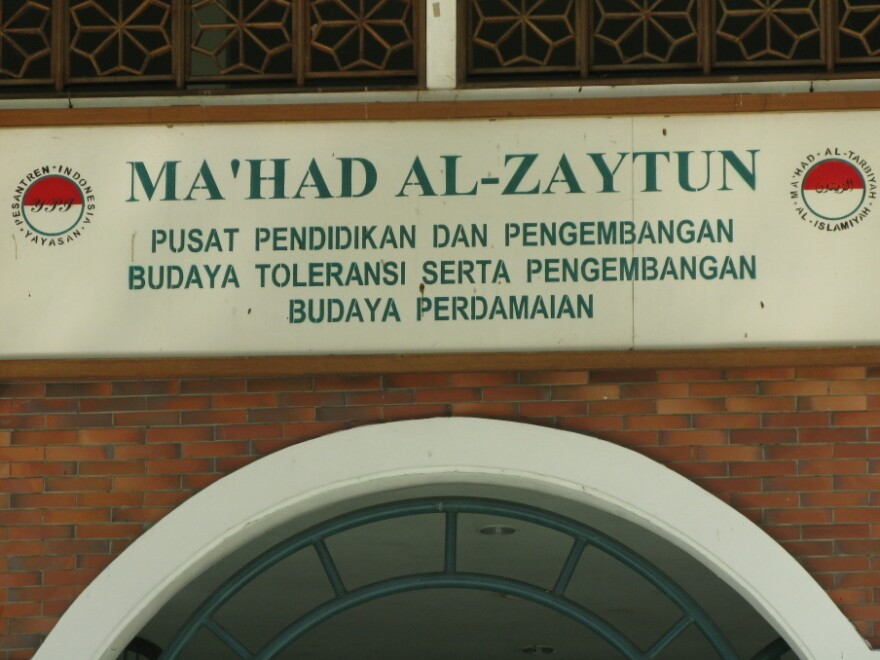 """The motto on a sign above the school's door emphasizes """"toleransi"""" or  tolerance toward people of other ethnic and religious groups."""