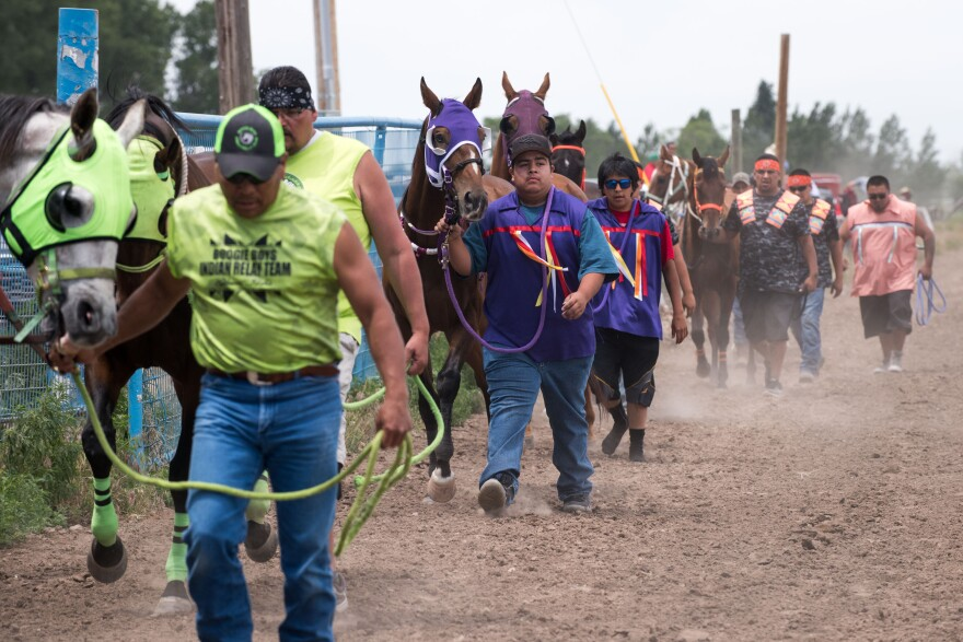 Photo of riders leading horses.