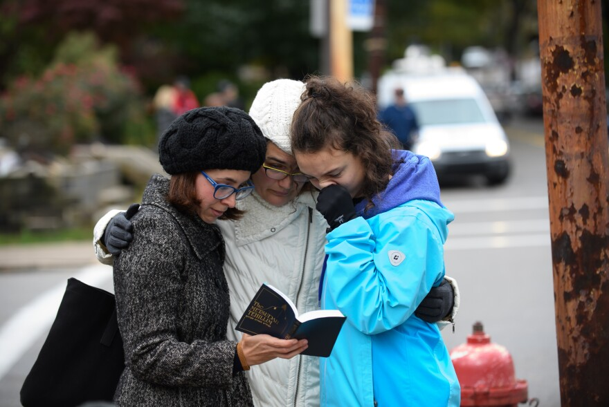 Tammy Hepps, Kate Rothstein and her daughter, Simone Rothstein, 16, pray from a prayerbook a block away from the site of a mass shooting at the Tree of Life Synagogue in the Squirrel Hill neighborhood.