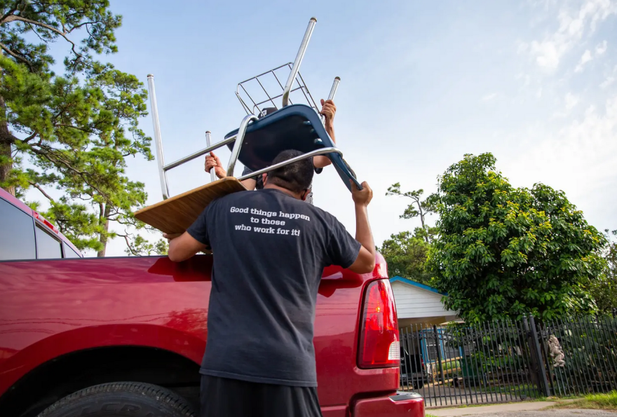 Jesus Sanchez, math instructor at Raul Yzaguirre School for Success, helps load chairs and desks into vehicles during the drive-thru giveaway.